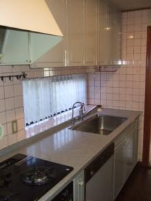 白を基調とした清潔感のあるキッチンと波模様のキッチンタイル